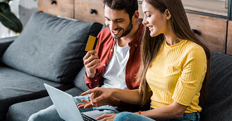 Couple browsing online store about to complete online purchase, with laptop in lap, man holding credit card