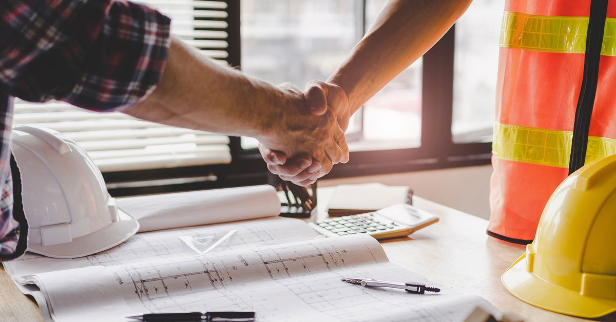 Contractor shaking hands with new hire in office