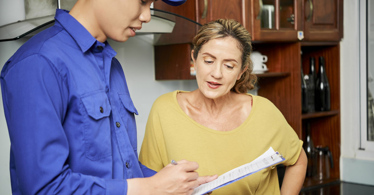 Woman reviewing maintenance contract with service technician