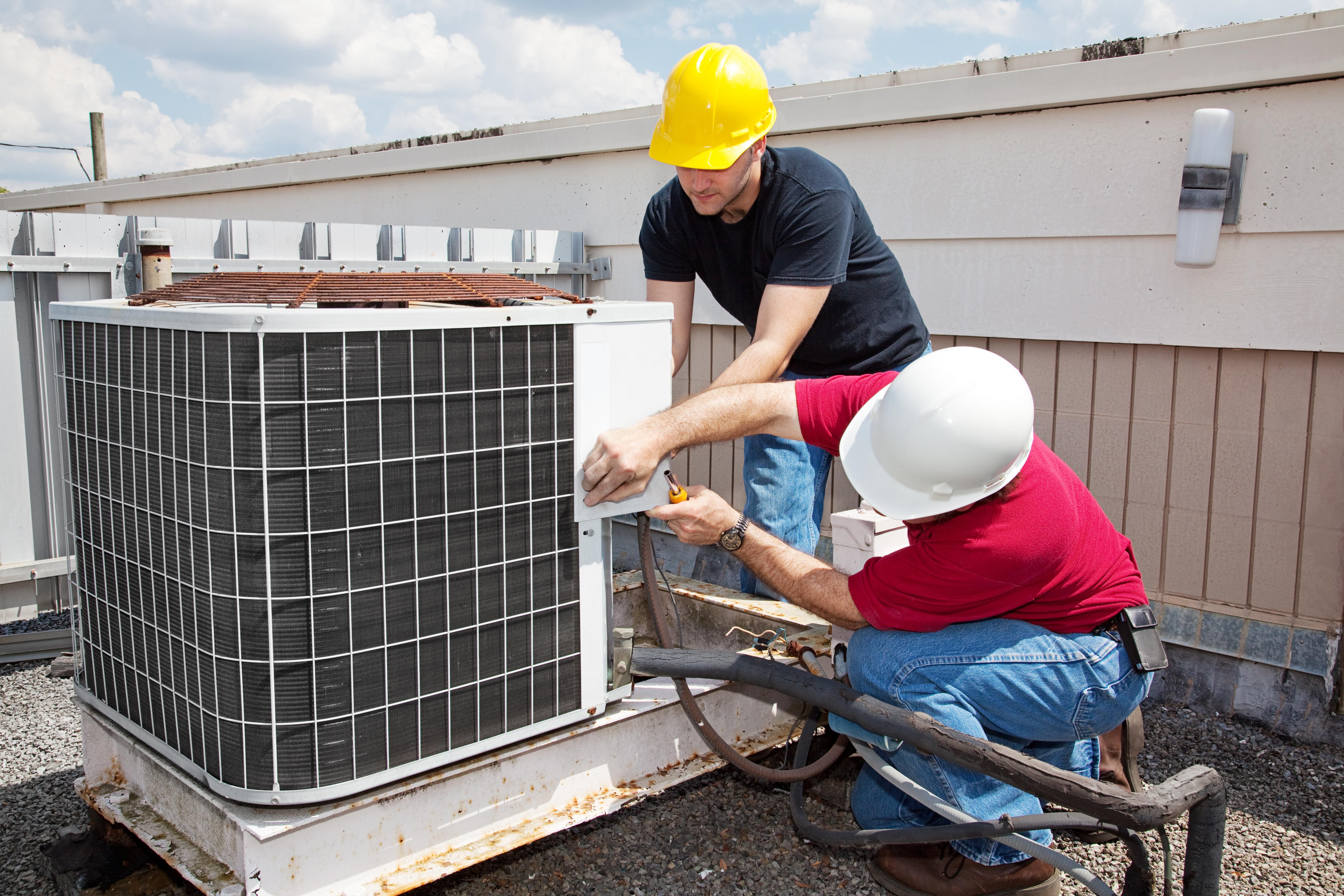 Men repairing HVAC unit on roof