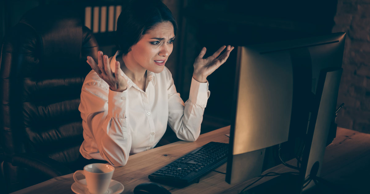 Woman staring at computer, frustrated, working late at night